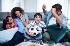 Семья смотря спичку совместно на телевидении стоковая фотография rf