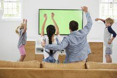 Семья смотря спорт на телевидении и веселить стоковая фотография