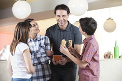Семья смотря среднего взрослого человека держа меню Стоковое Изображение