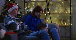 Семья смотря телевидение на Рожденственской ночи видеоматериал