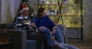Семья смотря телевидение на Рожденственской ночи сток-видео