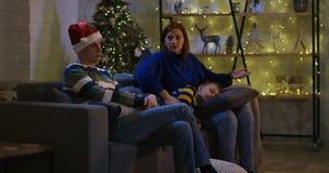 Семья смотря телевидение на Рожденственской ночи акции видеоматериалы