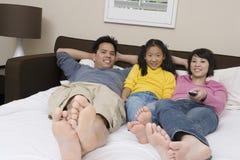 Семья смотря телевидение в кровати стоковые изображения rf