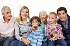 Семья смотря умное ТВ с дистанционным управлением Стоковое фото RF