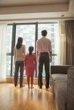 семья смотря через окно Стоковое Изображение