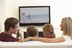 Семья смотря широкоэкранное ТВ дома