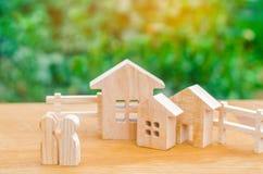 Семья стоит около их дома имущество принципиальной схемы реальное покупающ, продавать, арендуя дом Свойство insurance доступное h стоковые фото