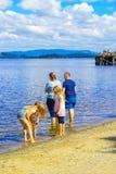 Семья стоя в воде на лете на Loch Lomond, Luss, Шотландии Стоковые Изображения