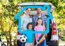 Семья стоя на дороге против плана дома в предпосылке Стоковые Изображения