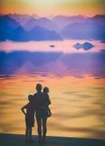 Семья стоя на пристани около озера горы Styl Instagram Стоковые Фотографии RF