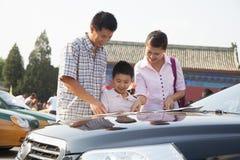 Семья стоя рядом с автомобилем и смотря карту Стоковое Изображение