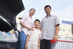 Семья стоя рядом с автомобилем с хозяйственными сумками Стоковое фото RF