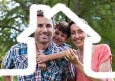 Семья стоя outdoors против плана дома в предпосылке Стоковое Изображение