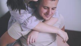 семья счастливая Девушка родителей детенышей славная и очаровательный парень лежат в пижамах на кровати рядом с их одн-год-старым акции видеоматериалы