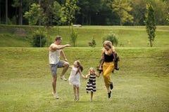 семья счастливая Дети и родители скачут на зеленую траву Стоковое Фото