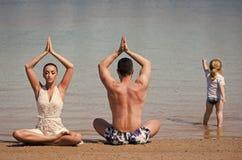 семья счастливая семья йоги человека, женщины и ребенк Стоковое фото RF
