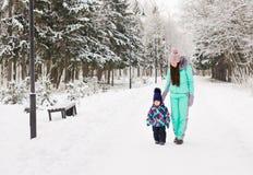 семья счастливая Девушка матери и ребенка на зиме идет в природу Стоковые Изображения RF