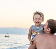 семья счастливая Молодой красивый отец и его усмехаясь ребёнок сына имея потеху на пляже моря, океана Положительное человеческое  Стоковое Изображение