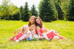 семья счастливая Молодые матери и дети мальчик и девушка на солнечный день Мамы и дети портрета на природе Положительные человече Стоковая Фотография