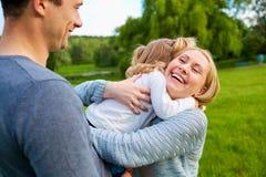 семья счастливая Счастливая мать обнимая ее ребенка усмехаясь, усмехающся Стоковое Фото