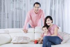 Семья счастливых улыбок азиатская на кресле стоковая фотография