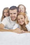 Семья ся пока кладущ на кровать покрытую с белым полотном Стоковая Фотография