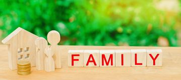Семья с деньгами стоит около их дома концепция жизни богатства и хорошо обеспеченное доходом счастливое ` семьи ` надписи на wood стоковое фото rf