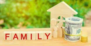 Семья с деньгами стоит около их дома концепция жизни богатства и хорошо обеспеченное доходом счастливое ` семьи ` надписи на wood стоковое фото