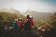 Семья с детьми путешествует пеший туризм в горах смотря взгляд стоковые изображения rf