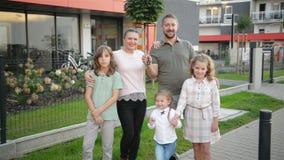 Семья с детьми смотря положение камеры на улице outdoors Пары и дети покупая новый дом Владельцы недвижимости сток-видео