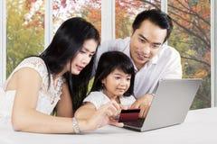 Семья с компьтер-книжкой и кредитной карточкой Стоковое фото RF