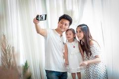Семья с маленькой девочкой в парке принимая selfie мобильным телефоном Стоковые Фото