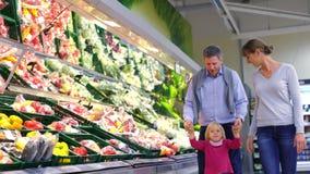 Семья с меньшим ребенком имея продукцию потехи покупая в супермаркете видеоматериал