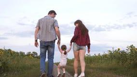 Семья с небольшими прогулками ребенка вдоль дороги и смеха рядом с полем солнцецветов Ребенок едет в оружиях его отца видеоматериал