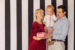 Семья с небольшой дочерью говоря розовым ретро телефоном, простой предпосылкой, счастьем и утехой стоковая фотография rf
