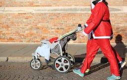 Семья с одеждами Санта Клауса идет с прогулочной коляской Стоковая Фотография