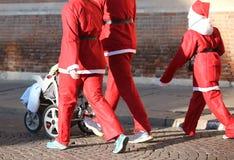 Семья с одеждами Санта Клауса идет с прогулочной коляской Стоковые Изображения