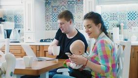 Семья с приборами пользы ребенка цифровыми на таблице завтрака видеоматериал