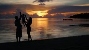 Семья с ребенком идущ и играющ на пляже во время захода солнца Силуэты акции видеоматериалы