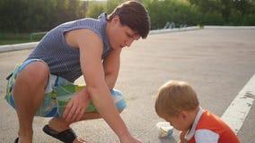 Семья с ребенком рисует с мелом на асфальте игры outdoors акции видеоматериалы