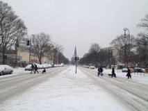 Семья с розвальнями пересекая улицу покрытую снегом с церковью ¼ SÃ dstern на заднем плане стоковые изображения