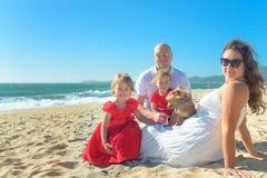 Семья с сестрами в красных платье и собаке на пляже Стоковые Фото