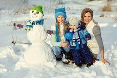 Семья с снеговиком Стоковая Фотография