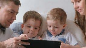 Семья с таблеткой Мама, папа и 2 малыша близнецов сыновьей смотря шарж на таблетке лежа на кровати сток-видео
