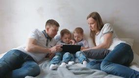 Семья с таблеткой Мама, папа и 2 малыша близнецов сыновьей смотря шарж на таблетке лежа на кровати видеоматериал
