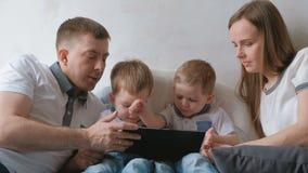 Семья с таблеткой Мама, папа и 2 малыша близнецов сыновьей смотря шарж на таблетке лежа на кровати акции видеоматериалы