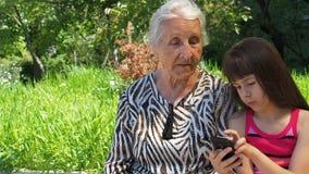 Семья с телефоном телефона Счастливая внучка показывает бабушке мобильный телефон Семья с мобильным телефоном в природе акции видеоматериалы