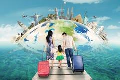 Семья с чемоданом и ориентир ориентиром мира Стоковое Изображение RF