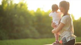 Семья тратит время в природе, матери нежно обнимая дочь, красивую маму играя с ее детьми в парке акции видеоматериалы