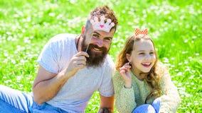 Семья тратит отдых outdoors, игры игры girlish Ребенок и отец представляя с атрибутами будочки кроны и фото смычка Стоковые Изображения RF